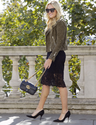 Bows & Sequins wearing a black lace dress, suede moto jacket, Kate Spade pumps, and a Gucci bag.