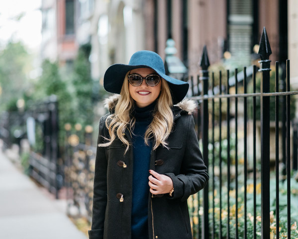 Bows & Sequins styling a fall outfit: fur-trimmed Cole Haan toggle coat, floppy wide-brim hat, Tom Ford cat eye sunglasses, and a cashmere Equipment turtleneck.