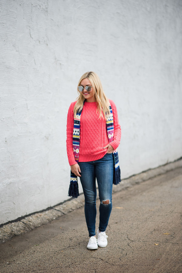 Bows & Sequins wearing a neon pink sweater with a fair isle scarf and white sneakers