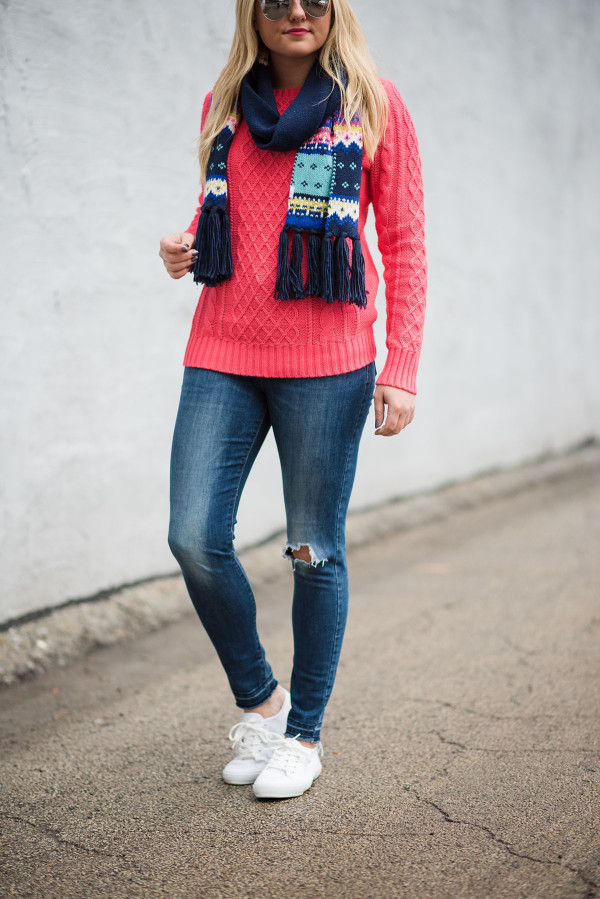 Bows & Sequins wearing a pink sweater, jeans, and a colorful scarf.