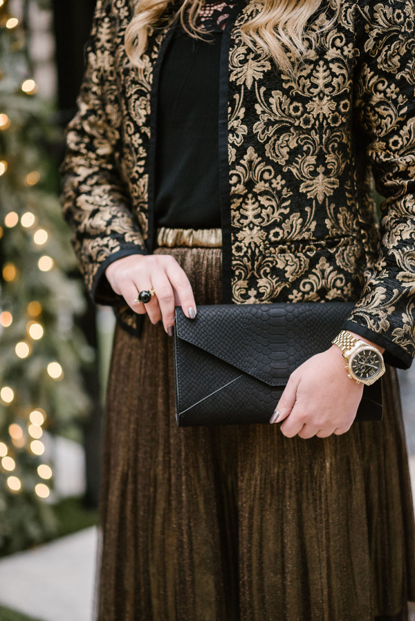 Bows & Sequins wearing a black and gold jacket with a gold skirt.