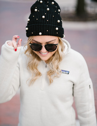 Bows and Sequins wearing a pearl beanie, Karen Walker sunglasses, and a Patagonia pullover.
