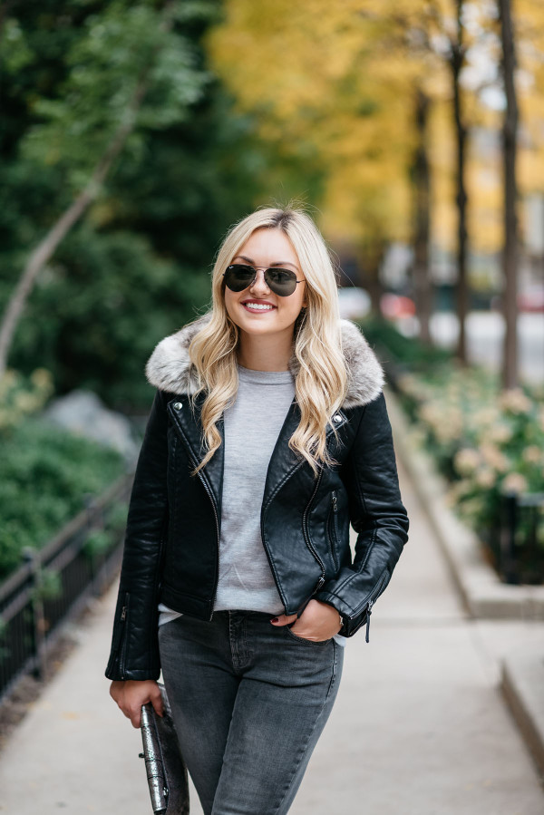 Jessica Sturdy wearing a black leather moto jacket with a faux fur collar, a grey J.Crew cashmere tee shirt, dark grey skinny jeans, and black Ray-Ban aviators.