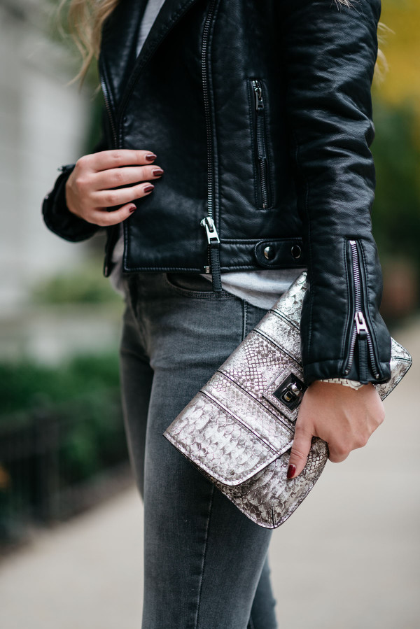 Bows & Sequins wearing a monochromatic black and grey outfit: black leather moto jacket, grey sweater, dark grey skinny jeans, and a metallic gunmetal clutch.