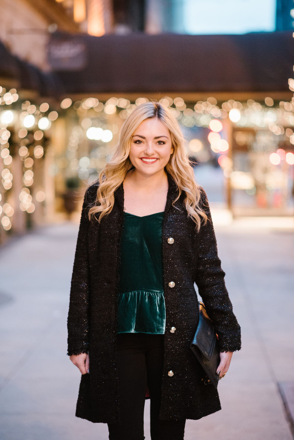 Bows & Sequins wearing a black tweed coat, green velvet peplum top, and black pants for a casual holiday outfit.
