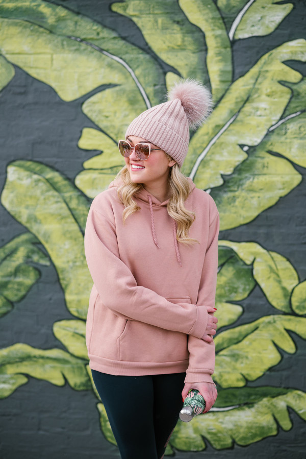 Bows & Sequins wearing a blush pink beanie, sunglasses, and sweatshirt.