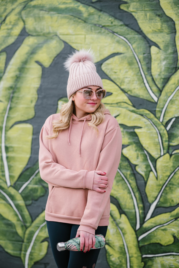 Bows & Sequins wearing a pink beanie, rose gold sunglasses, and a pink sweatshirt.