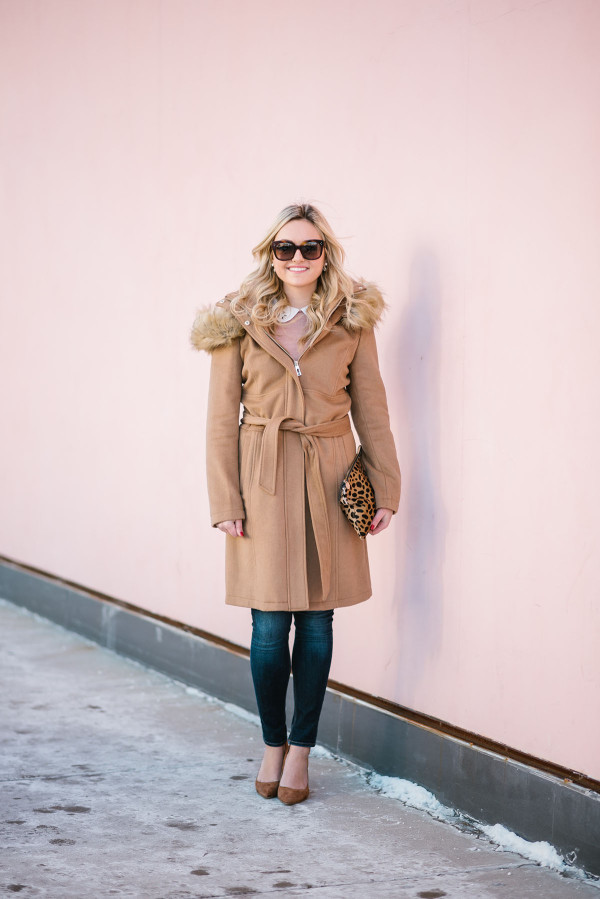 Bows & Sequins wearing a camel-colored long wool coat with a faux fur trimmed hood.