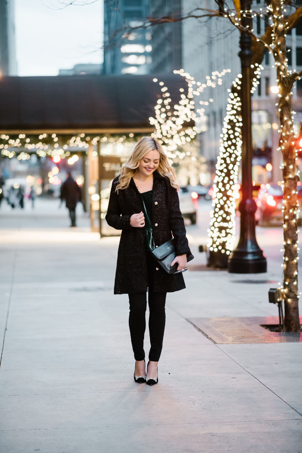 Bows & Sequins styling a simply holiday outfit: black tweed coat, emerald green velvet top, black pants, and black bow pumps.