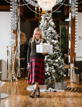Bows & Sequins styling an outfit perfect for a casual holiday party or Christmas with family! Green chenille sweater layered over a plaid dress with heels and pearls!