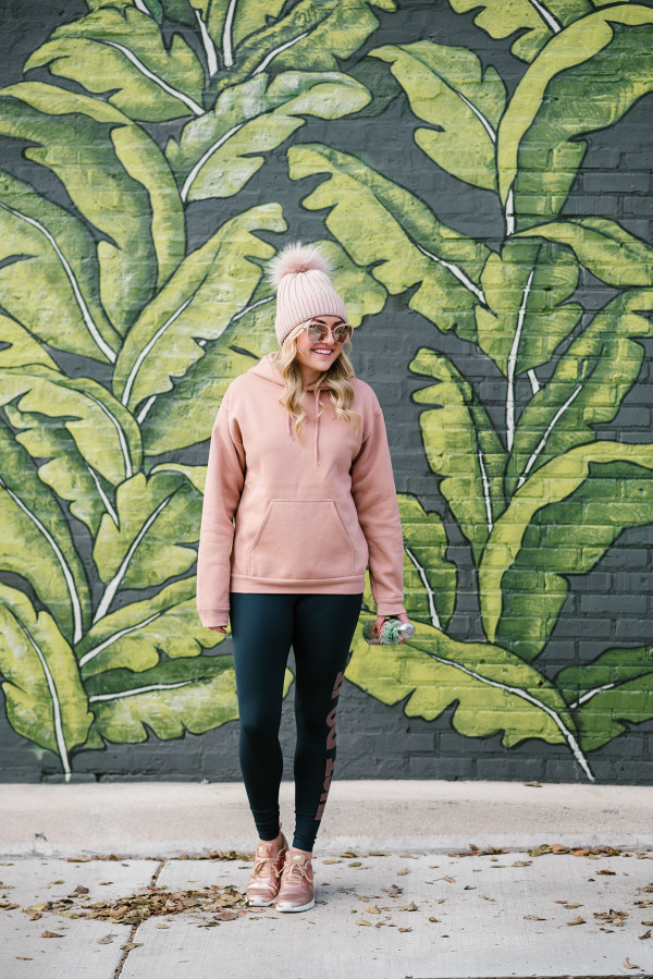 Bows & Sequins wearing cold weather workout wear in front of the palm leaf mural at Eden Chicago.