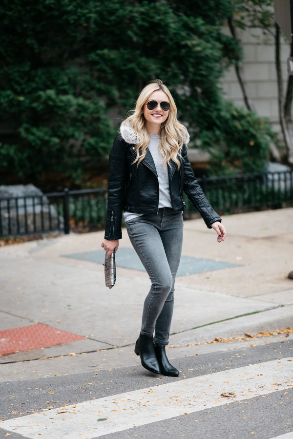 Jessica Sturdy of the fashion-focused lifestyle blog, Bows & Sequins, wearing a leather moto jacket with a fur collar, a grey cashmere tee shirt, dark grey skinny jeans, and flat black ankle booties in Chicago.