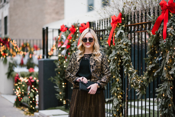 Bows & Sequins wearing a black and gold jacquard jacket, black lace yoke top, and a gold skirt for a Chirstmas party during the holiday season.