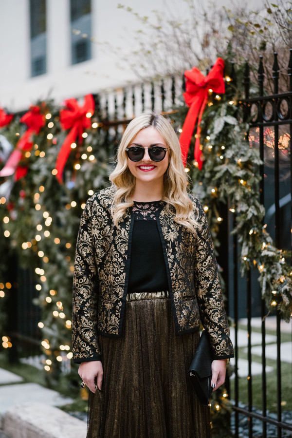 Bows & Sequins wearing a black & gold jacket, black lace top, and gold skirt for a holiday party outfit.