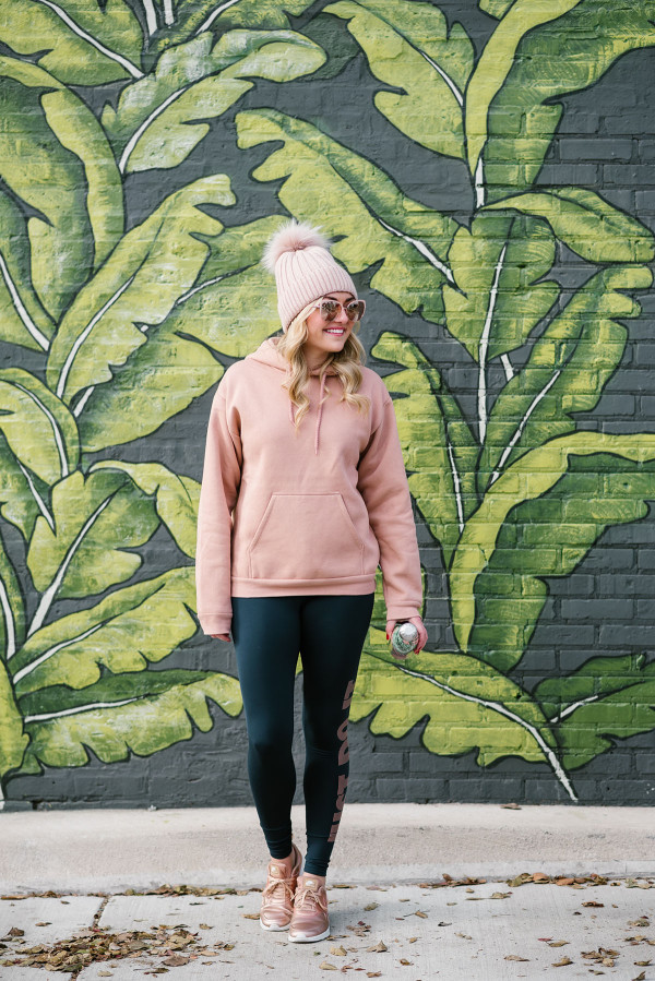 Chicago-based blogger, Jessica Sturdy, wearing a pink and navy workout outfit in front of the palm leaf wall at Eden in the West Loop.