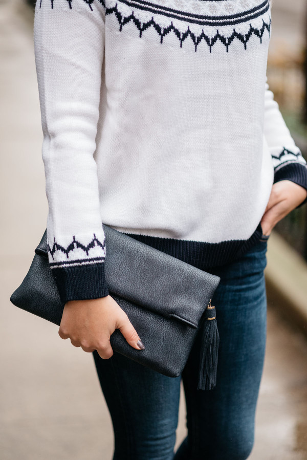 Bows & Sequins wearing a fair isle sweater and navy blue leather tassel clutch.