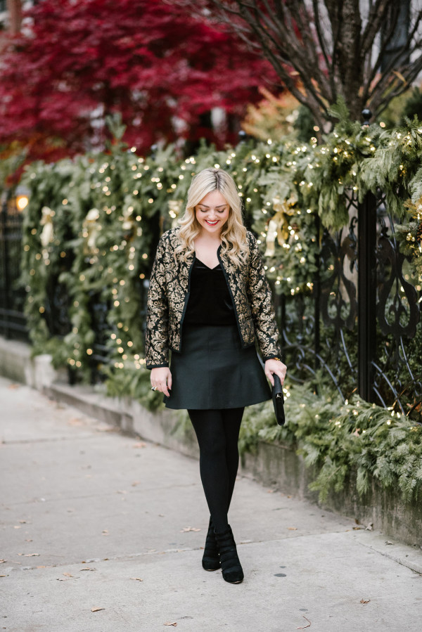 Bows & Sequins wearing a black & gold jacket, black velvet cami, fluted skirt, black tights, and strappy pumps for a New Years Eve outfit.