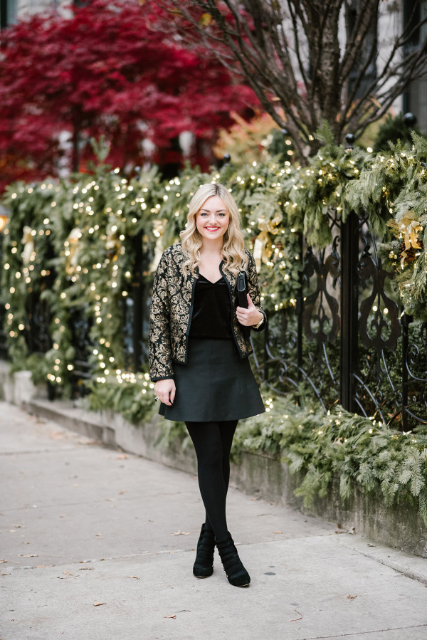 Bows & Sequins wearing a black & gold jacket, black velvet cami, fluted skirt, black tights, and strappy pumps for a holiday party outfit.
