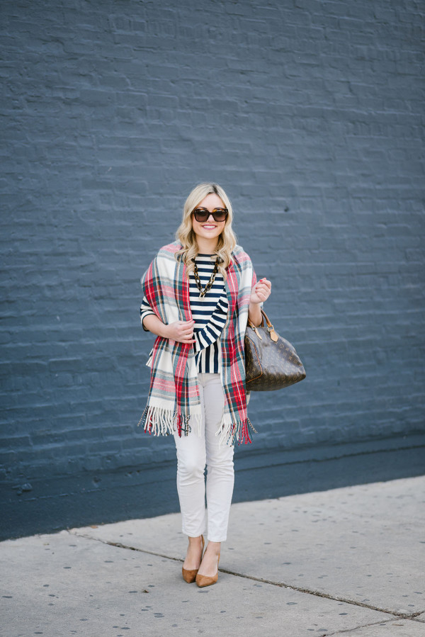Bows & Sequins wearing a plaid blanket scarf over a striped top and white corduroy jeans.