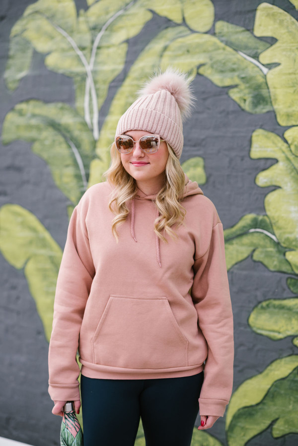 Bows & Sequins wearing a blush pink fur pom pom beanie, rose gold sunglasses, and a pink sweatshirt at Eden Chicago.
