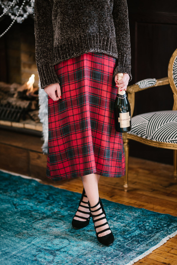 Bows & Sequins wearing a green chenille sweater over a plaid dress with strappy heels and a bottle of Chandon bubbly.