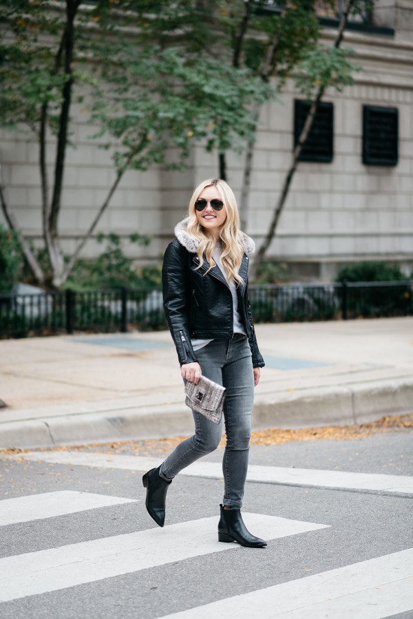 Bows & Sequins wearing a leather moto jacket with a removable faux fur collar, grey jeans, and flat black ankle booties in Chicago.