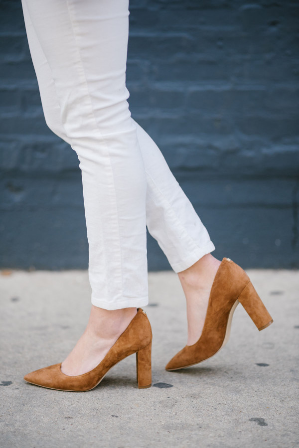 Bows & Sequins wearing a pair of white corduroy jeans with cognac suede pointed toe pumps.
