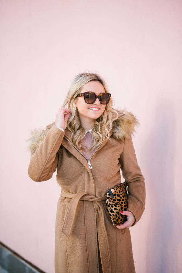 Bows & Sequins wearing a camel-colored coat with a faux-fur trimmed hood.