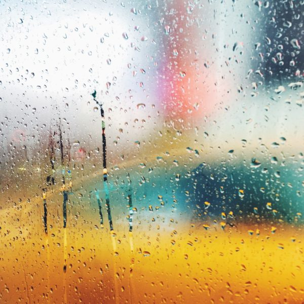 The view from a rainy New York City cab window with a yellow taxi.
