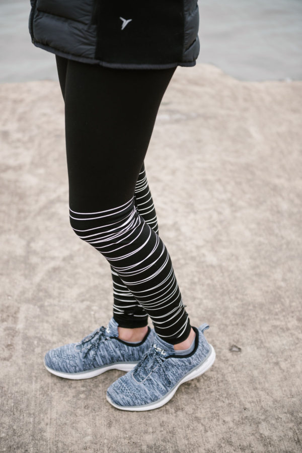 Bows & Sequins wearing black and white printed workout leggings and APL sneakers.