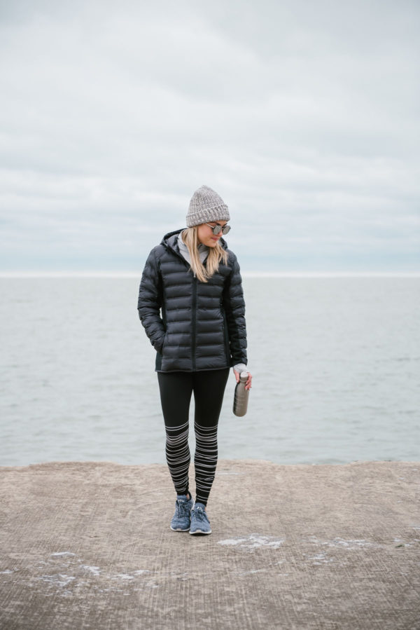 Bows & Sequins wearing a gray beanie and a black puffer coat for a winter workout.