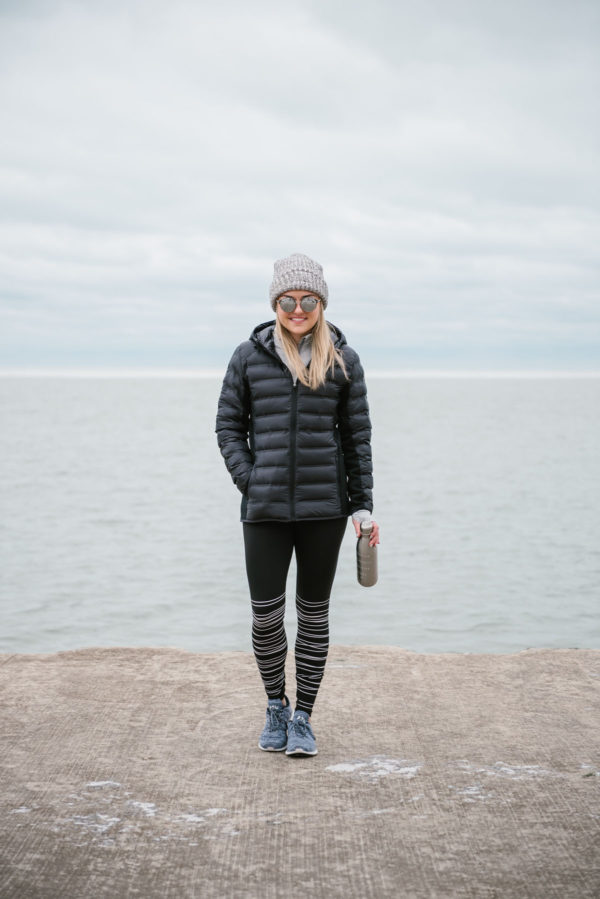 Bows & Sequins styling a black puffer jacket for winter workouts outside.