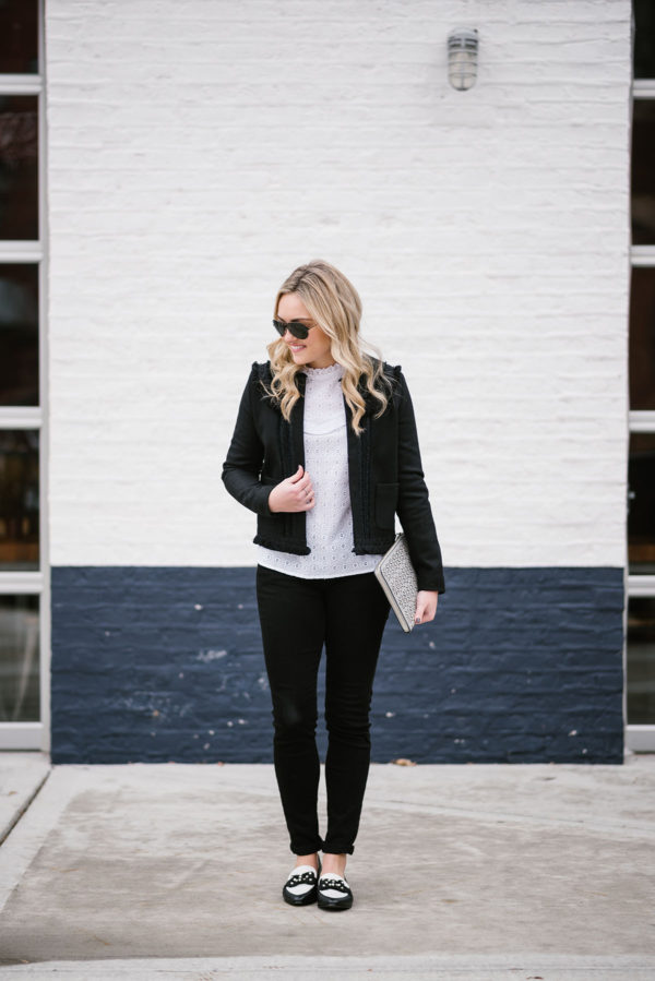 Bows & Sequins styling a black jacket and white lace top from Sezane with black jeans and bow loafers.