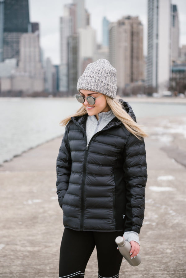 Bows & Sequins wearing a black puffer coat, a grey beanie, and mirrored sunglasses in front of the Chicago skyline at Oak Street Beach.