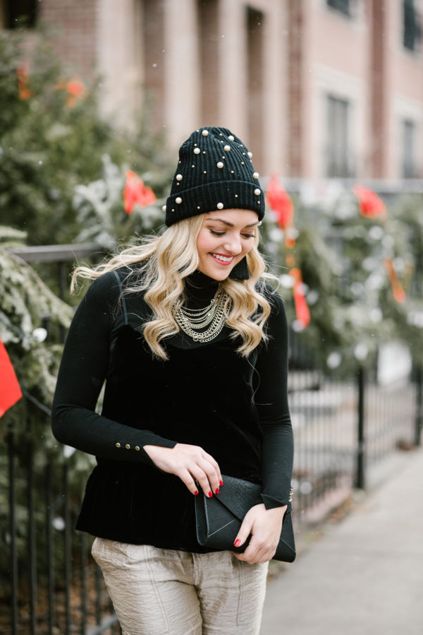 Bows & Sequins wearing a black and gold holiday outfit: black turtleneck, black velvet cami, gold pants, and a pearl embellished beanie.