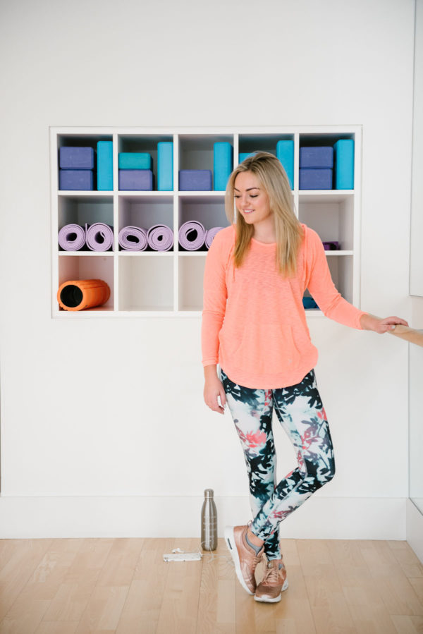 Bows & Sequins wearing a loose longsleeve tee and printed workout leggings in a fitness studio.