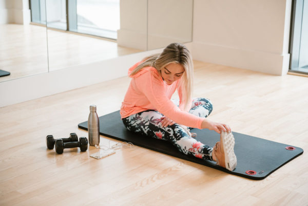 Bows & Sequins sharing her favorite ways to stay warm during winter workouts in coral top and flower-printed leggings