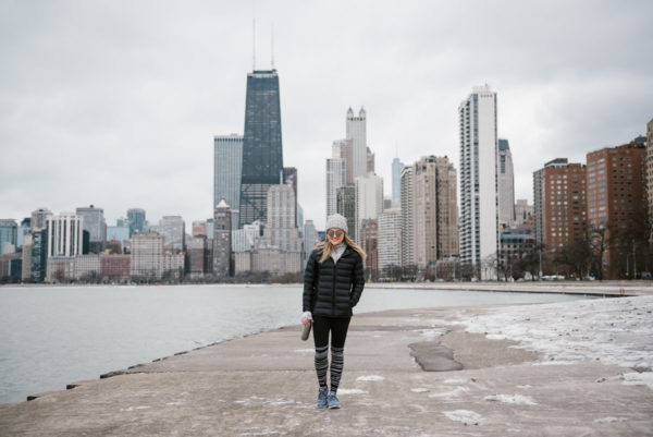 Bows & Sequins wearing a black puffer jacket and a grey beanie in front on the Chicago skyline at North Avenue Beach.