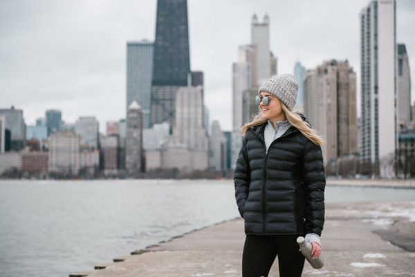 Bows & Sequins wearing a black puffer jacket by Lake Michigan in Chicago. Oak Street Beach has great views of the Chicago skyline!