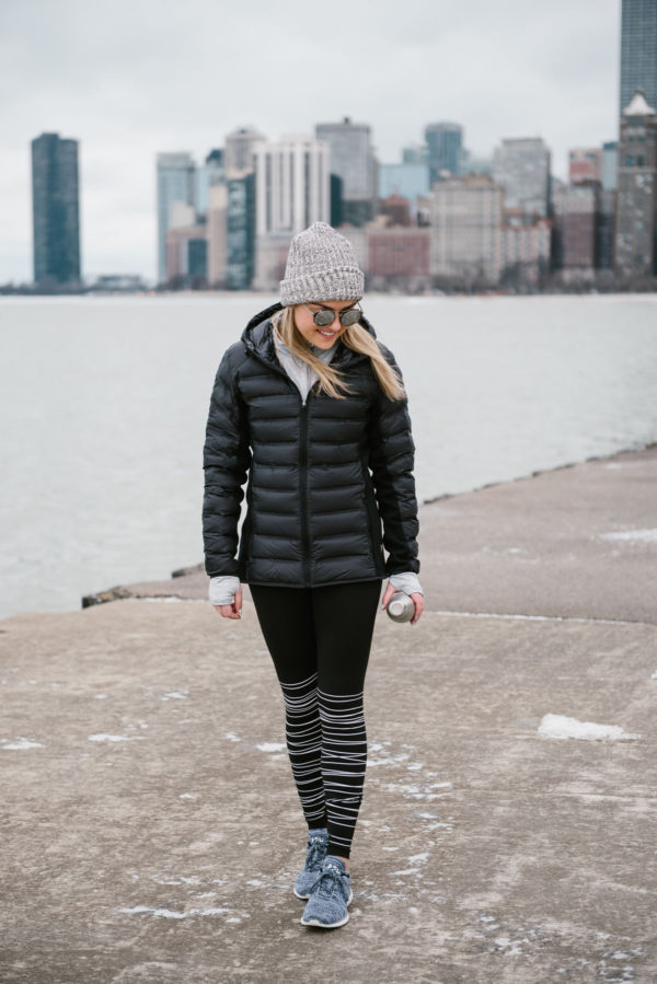 Bows & Sequins wearing a black puffer jacket and striped black and white leggings in front of the Chicago skyline by Lake Michigan.