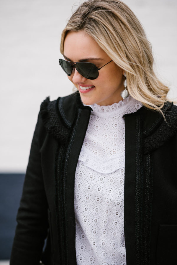 Bows & Sequins wearing black Ray-Ban aviators, BaubleBar Crispin Drops silver ball earrings, and a Sezane black jacket and lace blouse.