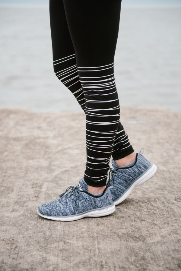 Bows & Sequins wearing black and white striped workout leggings with APL sneakers.
