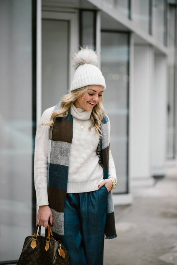 Bows & Sequins wearing a turtleneck sweater, a fur pom pom beanie, a checkered blanket scarf, and chambray wide leg pants.