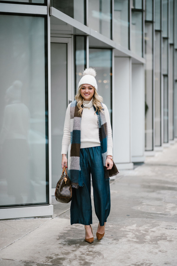 Bows & Sequins wearing a fur pom beanie, Uniqlo turtleneck sweater, chambray wide leg pants, pointed toe suede pumps, and a Louis Vuitton Speedy bag.