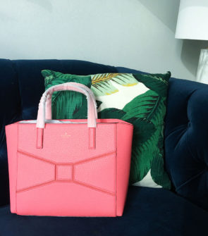 Bows & Sequins giving away a pink Kate Spade bow bag. Styled on a navy velvet sofa with a palm leaf pillow and marble lamp!