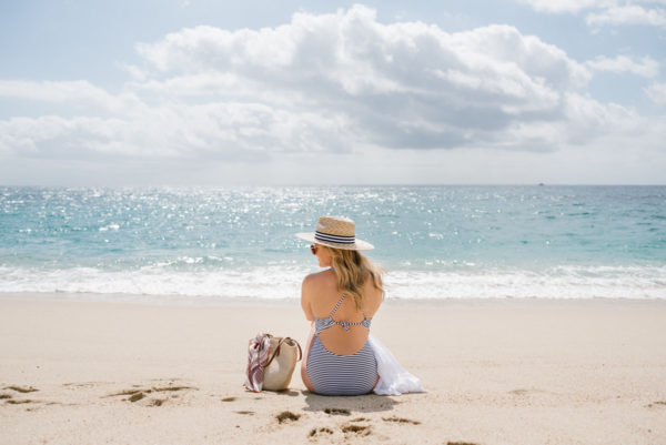 Lifestyle blogger Bows & Sequins wearing a striped swimsuit and straw hat on the beach in Cabo.