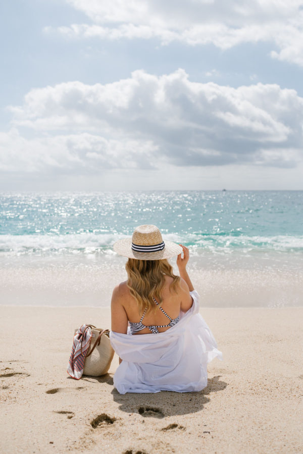 Travel blogger Bows & Sequins on a beach in Cabo, Mexico wearing an Azura oversized coverup with a Clare V straw tote and Jack Rogers sandals.