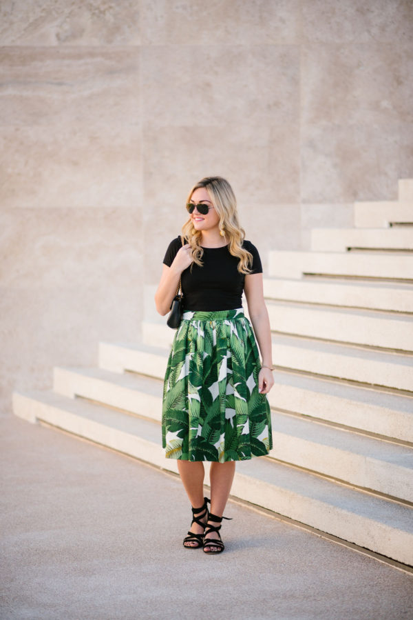 Bows & Sequins in a palm leaf patterned midi skirt with a black crop top and Ray-Ban aviators.