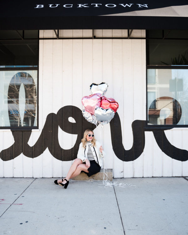 Bows & Sequins styling a black and white outfit for Valentine's Day in front of a LOVE wall.
