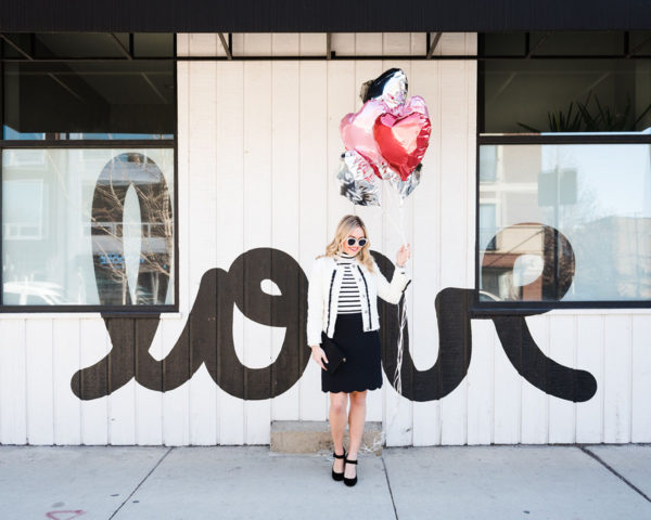Bows & Sequins styling a black and white outfit for Valentine's Day in front of a LOVE wall in Chicago.